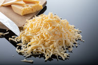Grated cheese and a piece of cheese on a wooden board