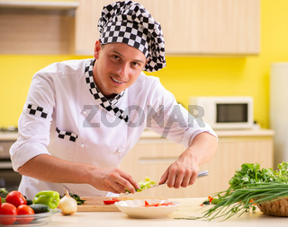 Young professional cook preparing salad at kitchen