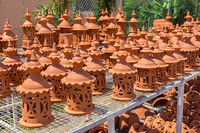 Many orange clay lanterns outside at pottery
