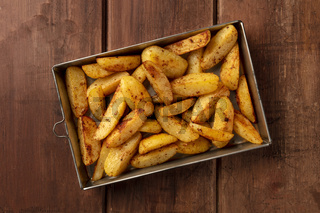 Potato wedges, oven roasted, shot from the top in a baking tray