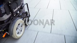 man on electric wheelchair driving on a street. Accessibility concept