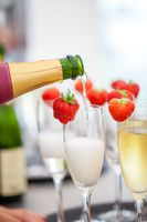 Sparkling wine or champagne and strawberry being poured out from the bottle