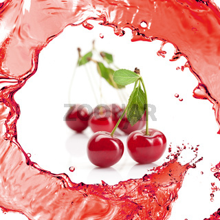 Red cherry with leaves and juice isolated on white