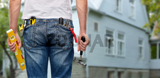 man with level and working tools in pockets