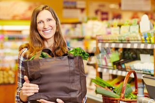 Lächelnde Frau trägt Einkaufstasche mit Gemüse