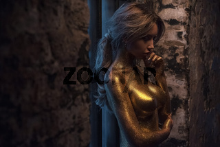 Nude woman in gold paint. Golden body art
