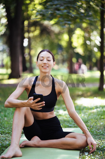 Fitness girl with a smartphone on nature background.