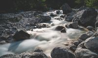 Motion blurred small waterfalls of a clear fresh mountain river in the alpine landscape, Austria