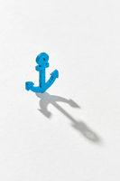 Blue emblem of anchor with long hard shadows.