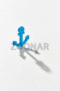 Blue emblem of anchor with long hard shadows.