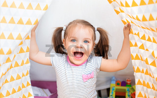 Delighted child laughing at home