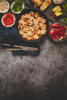 Grilled shrimps in cast iron grilling pan with fresh lemon, parsley, chili, garlic white wine sauce
