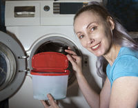 joyful woman in the background of a washing machine holds a box with washing gel in her hands