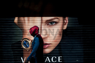 A Turkish Muslim woman wearing a red Hijab walking past an advertising poster on Istiklal Street