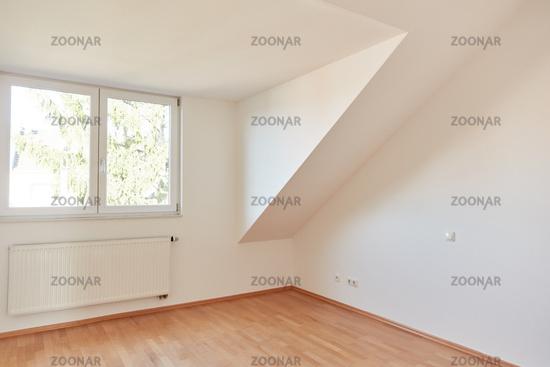 Leerer Raum in Dachgeschosswohnung mit Fenster und Heizung