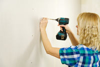 blond woman with screwdriver tool in hands working at home improvement. handywomen concept