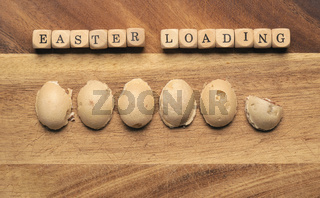 Wooden cubes with the inscription Easter loading, sweet Easter eggs as loading bar