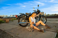 Sexy woman are repairing broken motorbike on the street at sunset.
