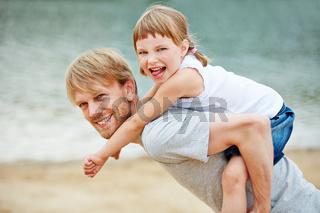 Vater und Tochter spielen am Strand