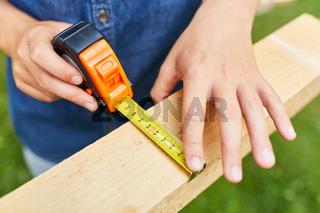 Hand von Kind mit Maßband beim Holz messen