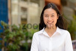Portrait of young beautiful Asian businesswoman outdoors