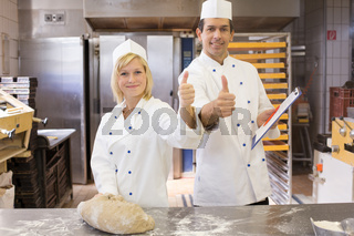 Two bakers with thumbs up in bakery