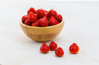 Full wooden bowl of fresh strawberries on white table