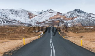 Rural empty  road leading to the  snowcapped mountains in Iceland