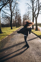 Portrait of a brunette girl having fun in a park in the rays of the bright sun.