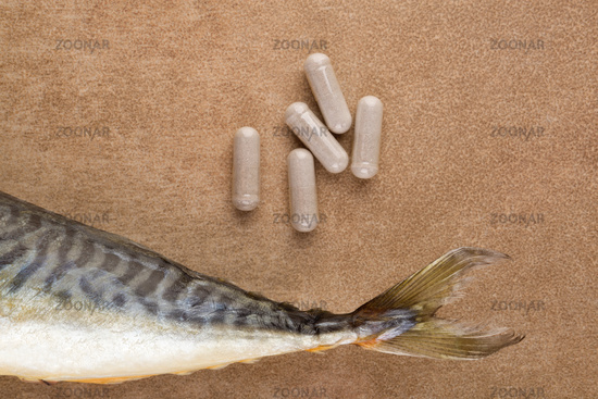 Fish collagen capsules and fresh fish tail with copy space from above.