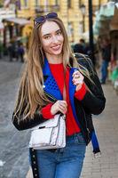 Beautiful white young woman wearing sunglasses, stylish sweater and leather jacket and handbag posing on the street, beautiful sexy stylish smile woman on urban background, white women in Big City,