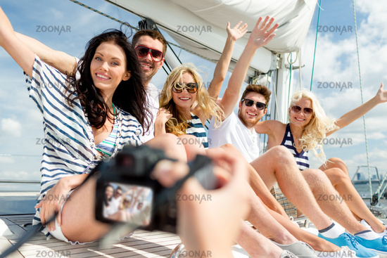 smiling friends photographing on yacht
