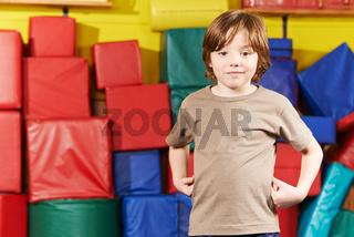 Junge steht in Turnhalle vom Kindergarten
