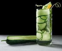 transparent glass with cucumber pieces, mint leaves and mineral water