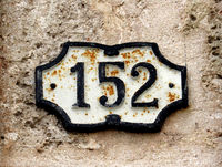 Vintage grunge square metal rusty plate of number of street address with number. Close up, brand.