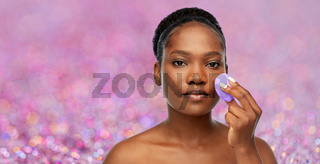 african american woman with make up sponge