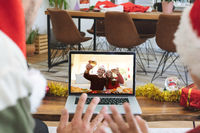Rear view of man and son in santa hats waving while having a videocall with couple in santa hats toa