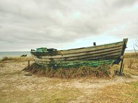 Small wrecked ship, wooden boat anchored at the sea