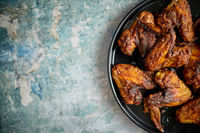 Grilled chicken wings on a black ceramic plate. Placed on a stone