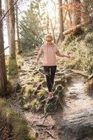 Active sporty woman running in autumn fall forest jumping over the roots on the path. Healthy lifestyle image of young active caucasian woman jogging outside in nature