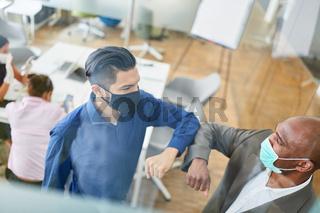 Geschäftsleute halten Abstand wegen Covid-19 im Büro
