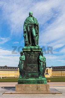 Monument of Karl Friedrich von Baden with Castle Karlsruhe in background and blue sky. Karlsruhe, Baden-Wuerttemberg, Germany