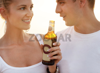 Couple on the beach having party, drinking and having fun in the sunset