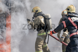 Firefighters extinguishes fire from fire hose, using fire-fighting water-foam barrel with air-mechanical foam