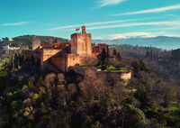 Aerial drone point of view Granada castle and surrounding lands meadows, Alhambra or Red Castle, located on top of hill al-Sabika, moorish famous place palace fortress complex in Andalusia, Spain