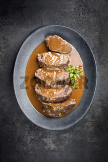 Traditional braised marinated German Sauerbraten from beef in spicy brown sauce as top view in a modern design cast iron plate with copy space