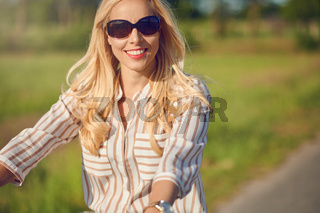 Portrait of woman riding a bicycle in a sunny day