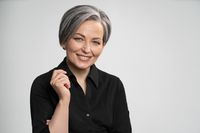 Charming gray haired woman wearing black shirt smiles at camera, isolated on white background. Mature Caucasian woman in studio raised her elbow bending arm. High quality photo