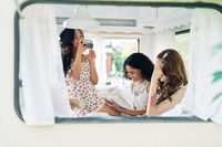 Beautiful woman making photo of her multi ethnic friends inside the camper van during their summer travel