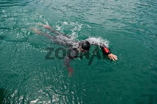 triathlon athlete swimming on lake wearing wetsuit